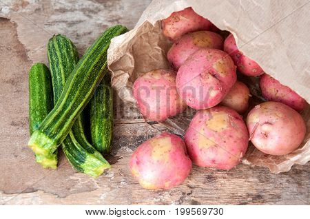 Red Potatoes In Paper Bag And Young Zucchini On Table