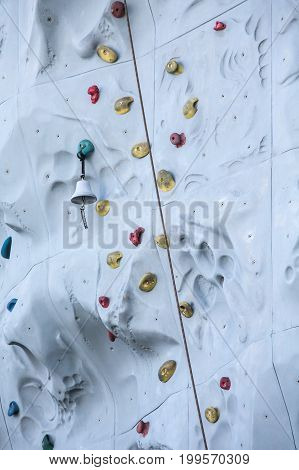 A rock climbing wall with ropes and bells to signal finishing