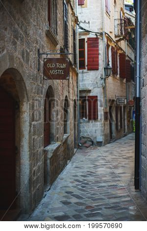 Narrow streets of the ancient city-fortress of the Mediterranean. Stone ancient houses and architecture of the Middle Ages. Details of architecture on a bright summer day. Travel to Montenegro, Kotor.