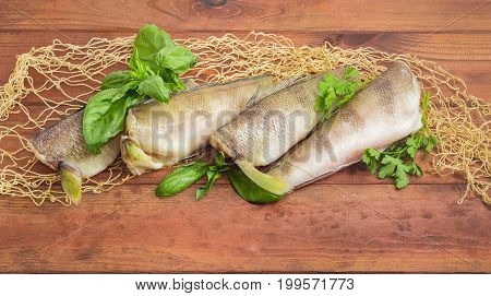 Several uncooked carcasses of the notothenia fish without od head and tail and twigs of basil and parsley on the fishing net on a dark wooden surface