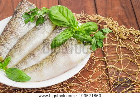 Fragment of a white dish with carcasses of the notothenia fish without of a heads and tails and with peeled scales basil and parsley twigs on a dark wooden surface with fishing net closeup