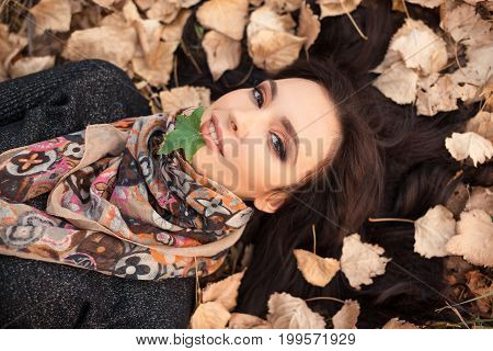 Autumn girl playing in city park. Portrait of an autumn woman lying over dry leaves and one green leaf in mouth outside in fall forest. Beautiful energetic mixed race Caucasian Asian young woman.