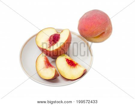 One whole ripe fresh peach and one cut into slices peach on a saucer on a white background