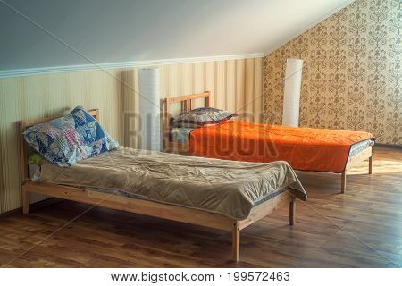 Two cozy beds with colorful linen in small hostel room