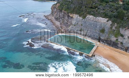 Aerial view of beachside swimming pool with waves and rock cliff at Bilgola in Sydney, Australia