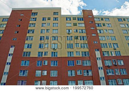 Facade of a large house with apartments and windows of brown color