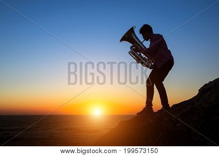 Musician silhouette play Tuba on sea shore at sunset.