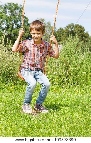 Happy little boy swinging on swing outdoor