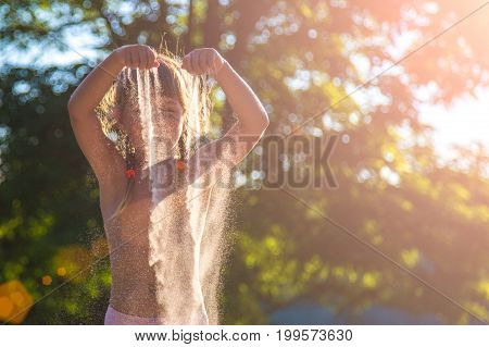 Young girl with sand in hands. Sand is wrapped in the sunset.