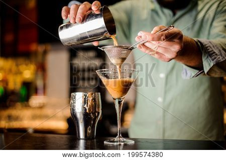 close up barmans hands with cocktail no face