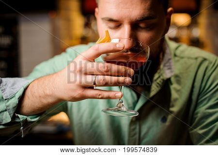 bartender is holdind cocktail with closed eyes