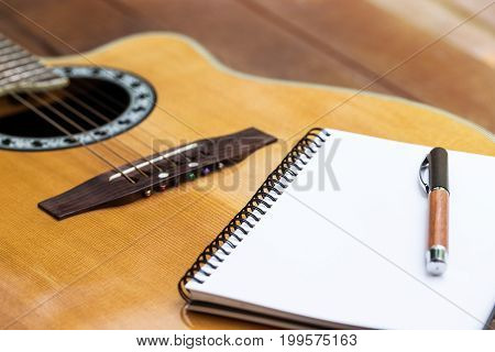 acoustic guitar with notebook and pen on wood background