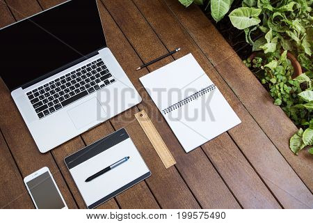 Workspace relaxing chill out work for office and design laptop smartphone pen tablet and other stationary on wood floor with plant