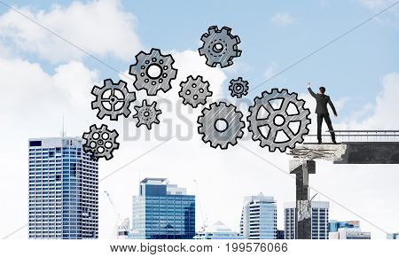 Businessman in suit drawing sketches of gear mechanism while standing on broken bridge with cityscape on background. 3D rendering.