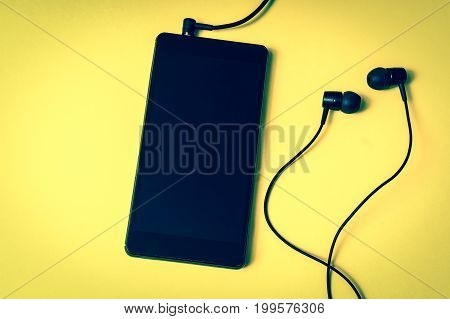 Mobile Phone With Headphones On Yellow Background
