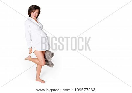 Pregnant woman holding soft toy. Pretty young woman carrying teddy bear. Free space for text