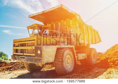 Quarry truck in sunlight, processes of extraction of clay and minerals in mine