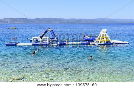 BRELA, CROATIA - 6 JULY, 2017: Inflatable slide on the sea for water activities.
