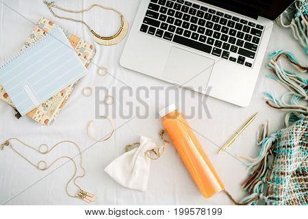 Feminine home office in bed with laptop diary fresh juice bottle woman accessories on white sheet and plaid. Flat lay top view home office background.