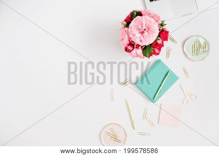 Flat lay home office desk with space for text. Female workspace with laptop pink and red roses bouquet golden accessories mint diary on white background. Top view feminine background.