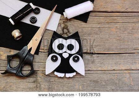 Stuffed felt owl toy, black and white felt sheets, scissors, threads, buttons on a vintage wooden background with copy space. Creating adorable owl toy from felt. Owl crafts idea for kids. Top view