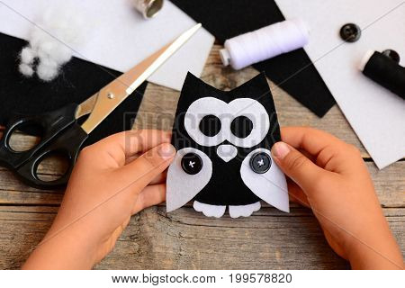 Child holds a felt owl toy in his hand. Small child made an owl out of black and white felt. Teaching children simple sewing skills at home. Sewing concept