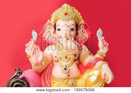Close-up picture of a statue or idol of figurine of Lord Ganesha made up of clay isolated over plain background