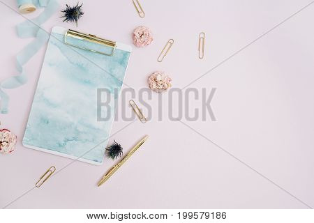 Flat lay of clipboard rose buds blue ribbon golden pen and clips on pale pink background. Top view stylish decorated mock up.