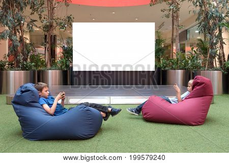 Mock up of blank advertising screen in modern shopping mall. Children with mobile phone near big blank digital screen