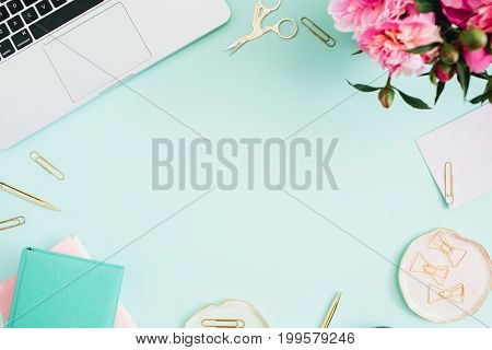 Flat lay home office desk. Female workspace with laptop pink peonies bouquet golden accessories pink and mint diary on mint background. Top view feminine background.
