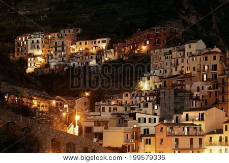 Italian style resident buildings over cliff in Manarola in Cinque Terre at night, Italy.