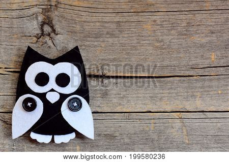 Stuffed felt owl isolated on a vintage wooden background with empty space for text. Owl stitched from white and black felt. Cute felt toy background