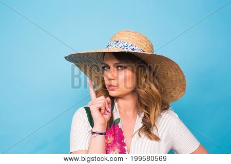 portrait of attractive young woman with finger on lips gesturing silence, studio shot.