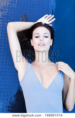 Beautiful brunette woman in a gray swimsuit near the pool. Portrait of a beautiful woman with long hair. Woman in the pool. A woman is sunbathing by the pool in a grey swimsuit. Girl with wet hair.