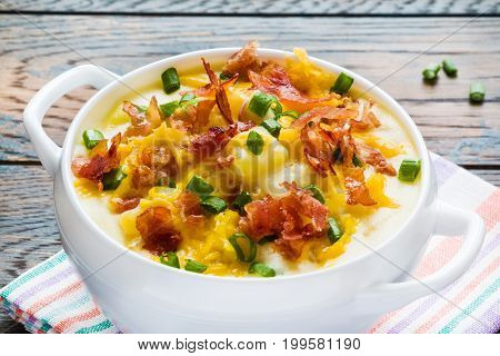 Easy homemade cheesy potato soup with bacon in a white bowl on the wooden rustic table.