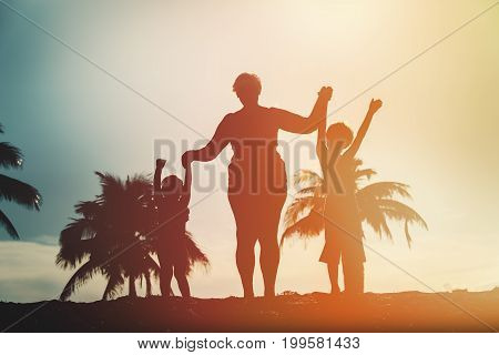silhouette of family with kids play at sunset tropical beach
