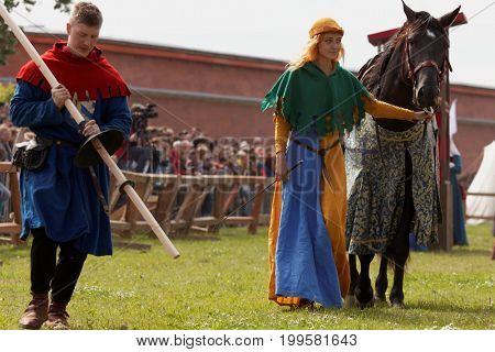ST. PETERSBURG, RUSSIA - JULY 8, 2017: People preparing a horse and a lance for participant of jousting tournament during the military history project Battle On Neva at St. Peter and Paul fortress