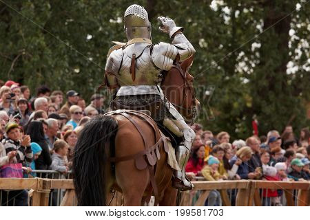 ST. PETERSBURG, RUSSIA - JULY 8, 2017: Armored knight on a horse participating in the jousting tournament during the military history project Battle On Neva at St. Peter and Paul fortress