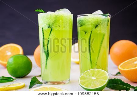 Natural transparent refreshing drink with cucumber, limes and orange