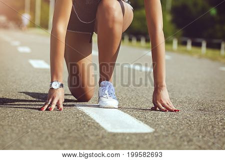 Action packed close-up image of a female athlete At low start for a sprint run on a track . The concept of a healthy lifestyle.