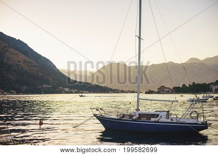 Sailing yacht moored at the shore at sunset. The magical view of the traveler to the sea: the sun at sunset, the mountains, the fjords and the yacht. Travel to Montenegro, Boko-kotorska bay.
