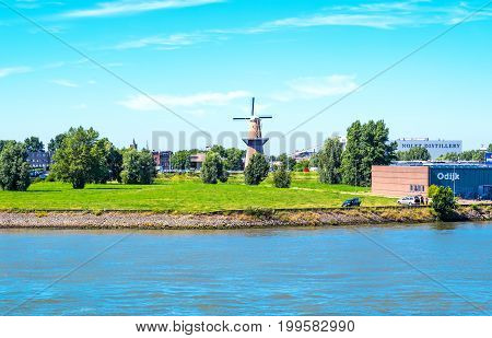 Rotterdam The Nederlands - July 18 2016: An old mill in the industrial area of the city seen from a boat crossing the Maas river