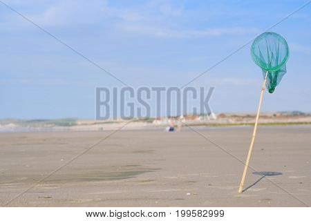 Catching green net in standing on sandy beach in france