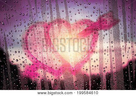 Heart shape with love on glass in rainy season.