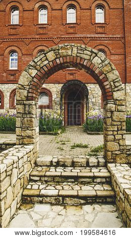 Brick Arch With Stairs In Front Of The Building With Windows