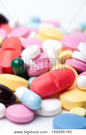Group of multicolored medical pills and capsules on white background. Colorful medicaments.