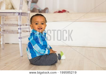 Full length portrait of a young mixed race boy sitting on the floor