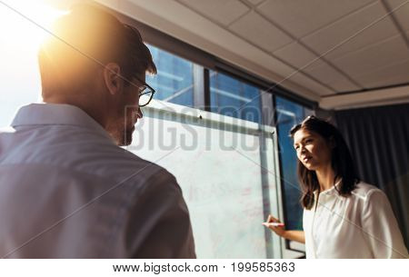Businesswoman writing ideas on whiteboard during discussion in boardroom. Two colleagues discussing business ideas in office.