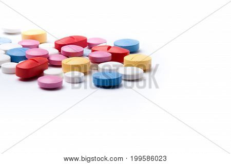 Heap of colorful medicine pills on white background with copyspace. Pharmaceutical medicaments.