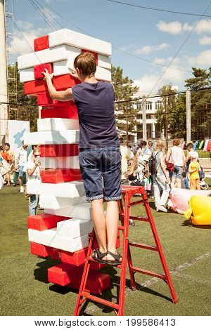 Khabarovsk Russia - August 13 2017: Young man play giant jenga game outdoors using a ladder. Person building a big tower of red and white bricks popular toy. Skills choices and risk concept